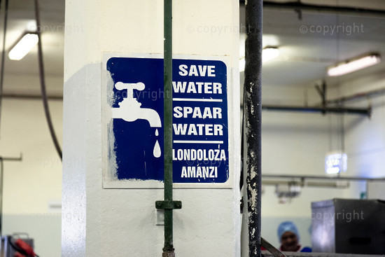 sign on factory wall indicating save water